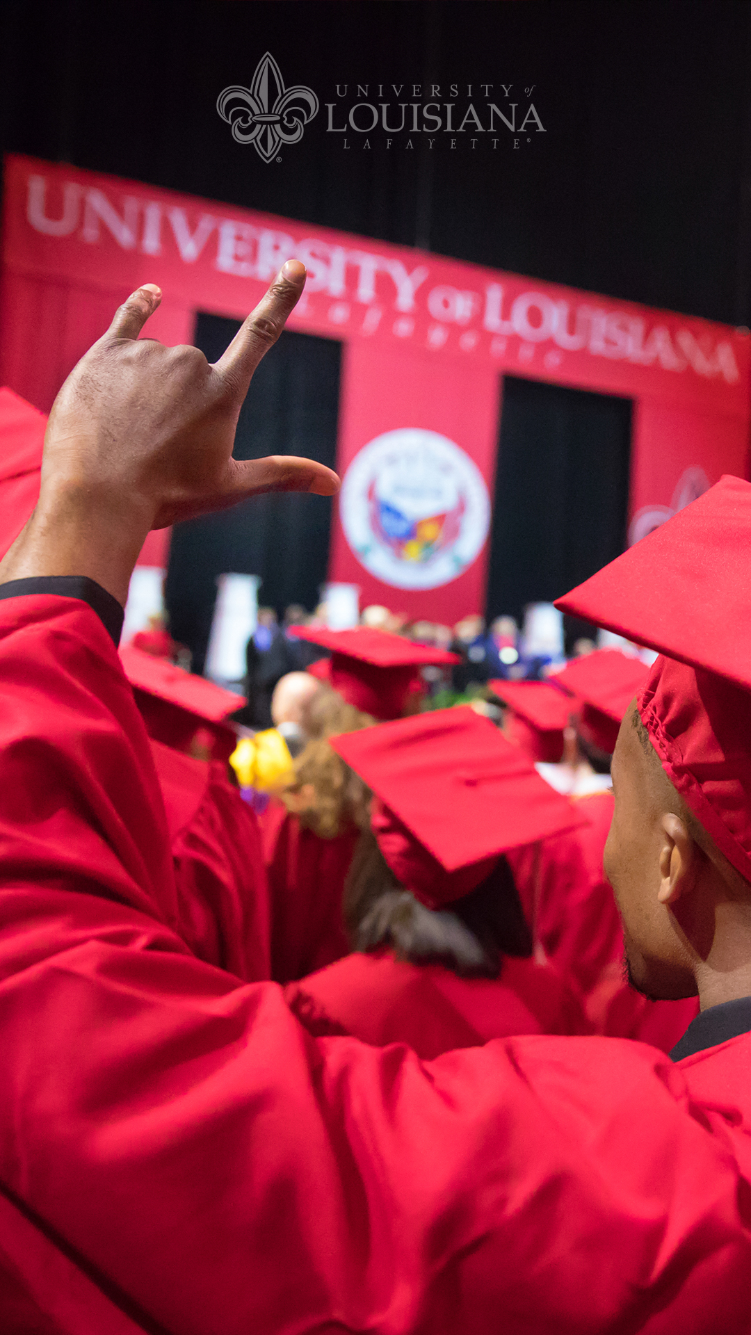 Photo of an African-American UL Lafayette graduate raising his hand in the UL hand sign in front of the University of Louisiana at Lafayette Commencement stage.